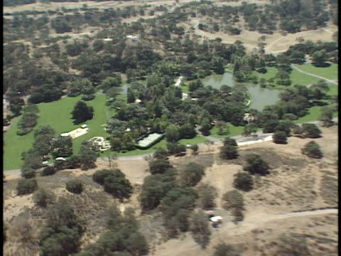 over michael jackson's neverland ranch south area, tennis court, pool area, partial main mansion . ca - ネバーランドバレーランチ点の映像素材/bロール