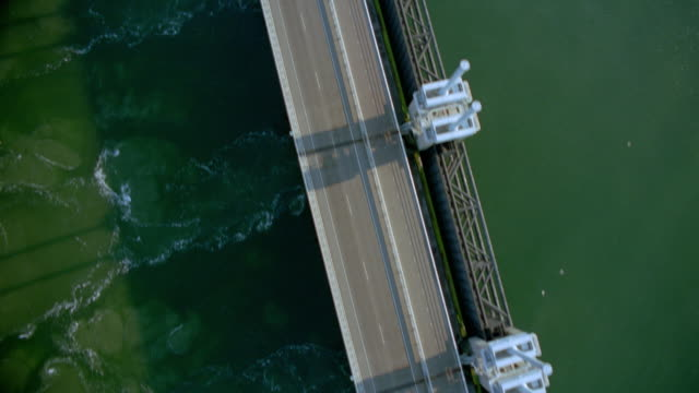 AERIAL over modern dike + hydroelectric equipment on river / Oosterscheldedam, south Holland