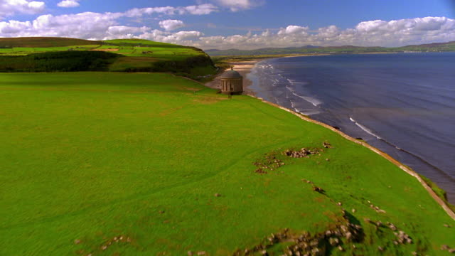 AERIAL over Mussenden Temple with beach + sea in background / Castlerock, County Derry, Northern Ireland