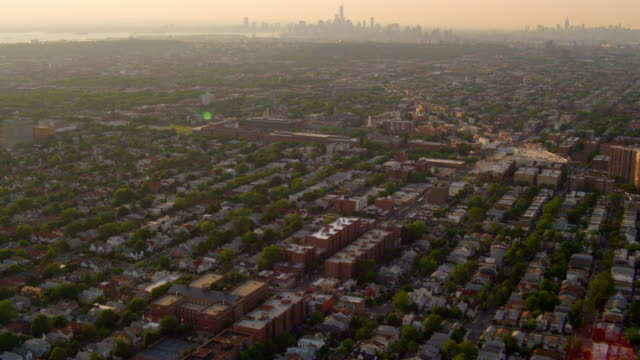 LONG AERIAL POV over neighborhoods in Brooklyn with TILT UP to distant Manhattan skyline in distant background