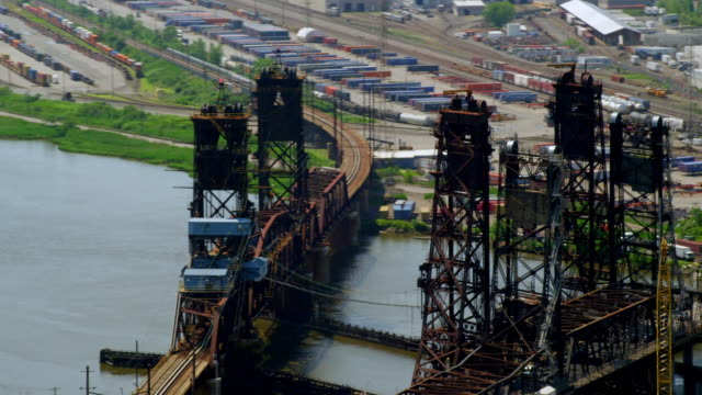 MEDIUM AERIAL over one vertical-lift bridge with traffic and two vertical-lift train bridges over water