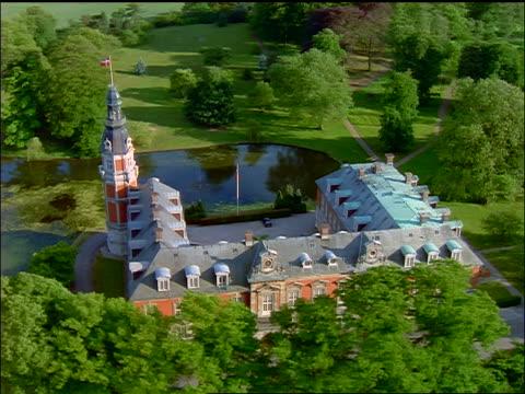 vídeos y material grabado en eventos de stock de aerial over ornate hveldholm slot building with danish flag / fyn, denmark - danish flag