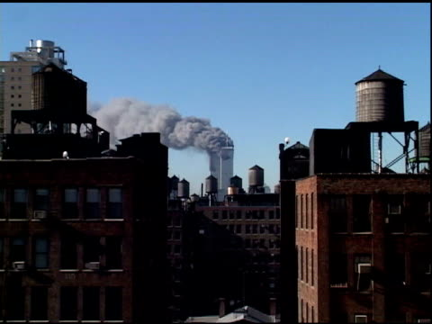 9/11/2001 zi over rooftops in manhattan to upper levels of wtc towers 1 2 on fire lots of dark smoke after both planes hit - world trade center manhattan video stock e b–roll