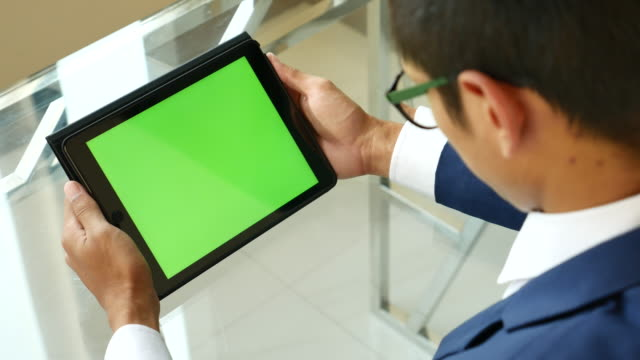 Over shoulder shot Businessman of Using digital tablet, Green screen