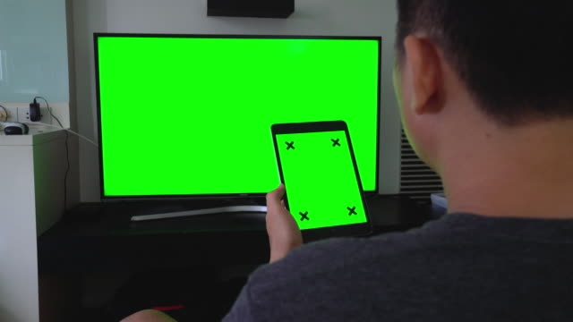 over shoulder shot of digital tablet and tv,green screen - large stock videos & royalty-free footage