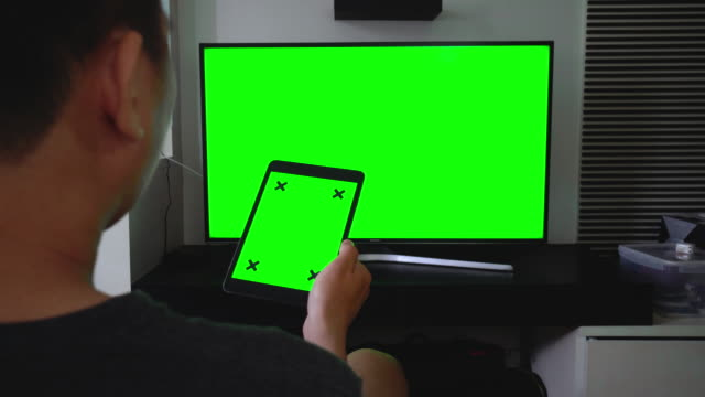 Over shoulder shot of digital tablet and TV,Green screen
