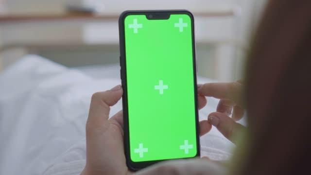 vídeos y material grabado en eventos de stock de sobre el tiro del hombro de paciente femenino usando el smartphone, pantalla verde - vista por la espalda
