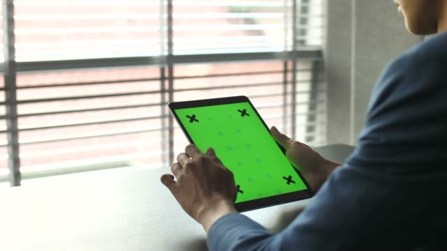 over shoulder shot of man using digital tablet with green screen in his office - using digital tablet stock videos & royalty-free footage