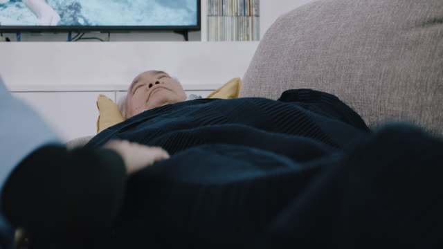 over shoulder shot of nurse putting blanket on senior man sleeping on sofa. - 70 79 years stock videos & royalty-free footage