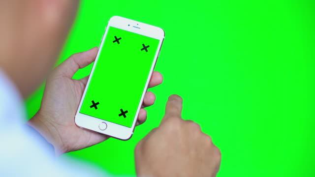 vídeos de stock e filmes b-roll de over shoulder shot of smart phone with green screen and green background - fundo verde