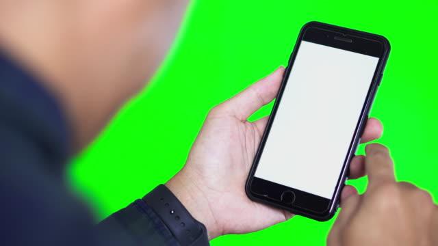 vídeos de stock e filmes b-roll de over shoulder shot of smart phone with white screen and green background - fundo verde
