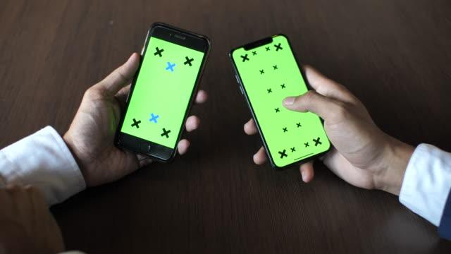 vidéos et rushes de sur coup d'épaule de deux personnes à l'aide de téléphone intelligent avec écran vert, gros plan - deux personnes