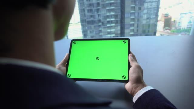 vídeos de stock, filmes e b-roll de sobre o ombro disparado de usar a tabela digital - panning