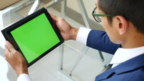 stockvideo's en b-roll-footage met over de schouder schot van gebruiken digitale tablet, groen scherm - over shoulder
