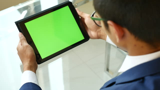 Over shoulder shot of Using digital tablet with Green screen, Chroma key