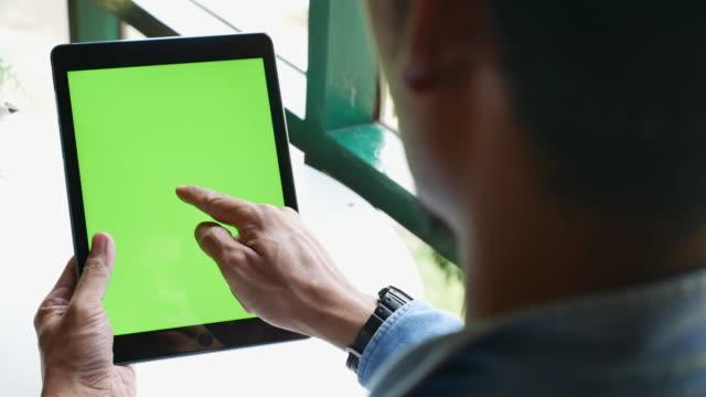 vídeos de stock, filmes e b-roll de sobre o ombro disparado de usar a tabuleta digital com tela verde - panning