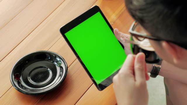Over shoulder shot of Using digital tablet,Green screen