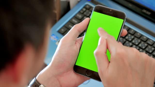 Over shoulder shot of Using smart phone,Green screen