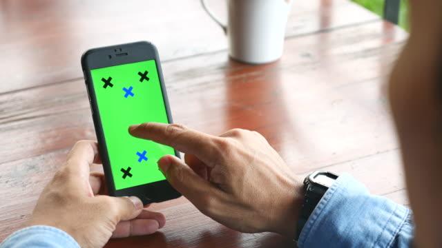 Over schouder slimme schot van gebruiken telefoon, groen scherm