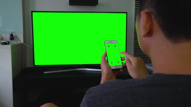 Over shoulder shot of using smartphone and TV,Green screen