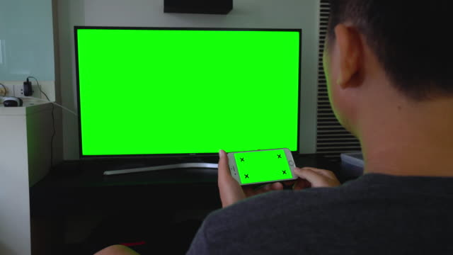 over shoulder shot of using smartphone and tv,green screen - computer monitor back stock videos & royalty-free footage