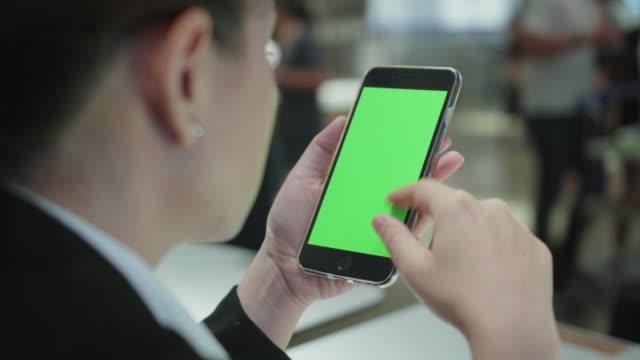 vídeos de stock, filmes e b-roll de por causa de dose de ombro de usando o smartphone em cafeteria, tela verde - rolando