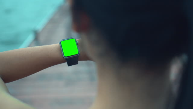 Over shoulder shot of Woman jogging and looking at smart watches,Green screen