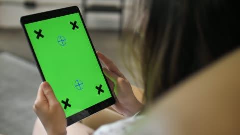 stockvideo's en b-roll-footage met over de schouder shot van de vrouw met behulp van digitale tablet, groen scherm - over shoulder