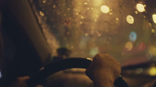 over shoulder shot of women driving a car in the rain at night - steering wheel stock videos & royalty-free footage