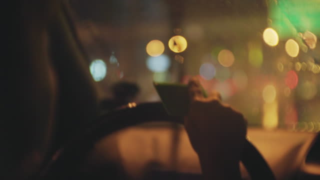 over shoulder shot of women driving a car in the rain at night - parking ticket stock videos & royalty-free footage