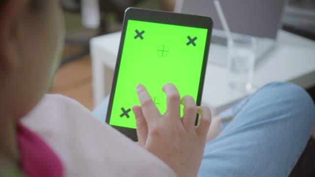 Über Schulter Schuss von Frauen mit digital-Tablette, Green-screen