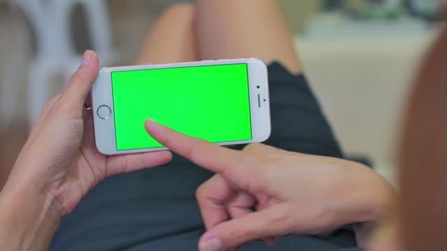 Sobre tiro de hombro de las mujeres que usan el teléfono inteligente, pantalla verde