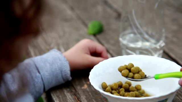 stockvideo's en b-roll-footage met schouder weergave van een kind eten groene erwten - handen in een kommetje