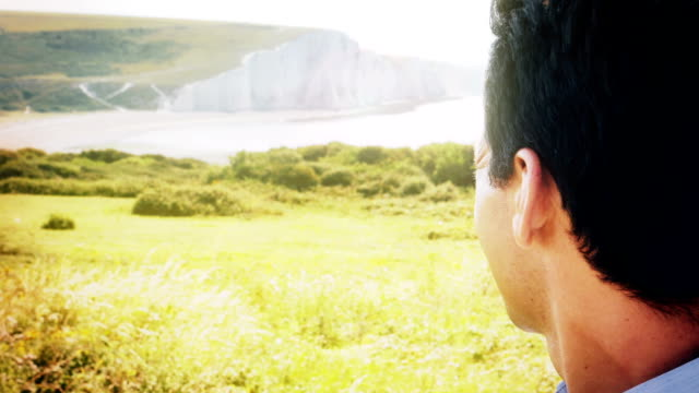 Over shoulder view of cliffs and sea at Cuckmere, East Sussex, England. Slow mo. WS.