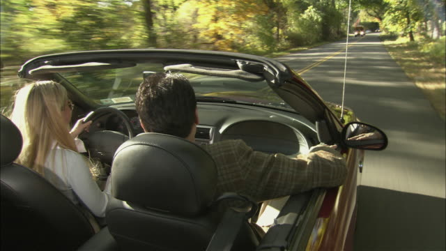 vídeos y material grabado en eventos de stock de ms ts over shoulder view of man and woman in convertible as they drive on tree-lined road / long island, new york, usa - long island