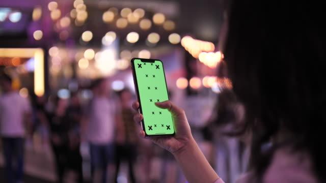 stockvideo's en b-roll-footage met over schouder beeld van vrouw met behulp van smart phone groen scherm 's nachts - menselijke hand