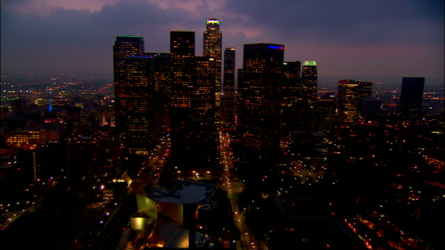 aerial over skyscrapers in downtown los angeles and staples center lit up at dusk / california - straßenüberführung stock-videos und b-roll-filmmaterial