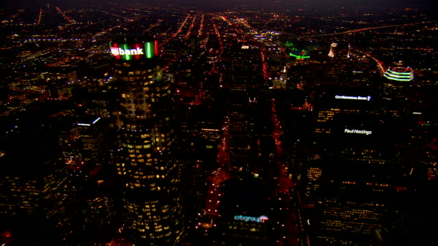 AERIAL Over skyscrapers in downtown Los Angeles towards Staples Center at night / California