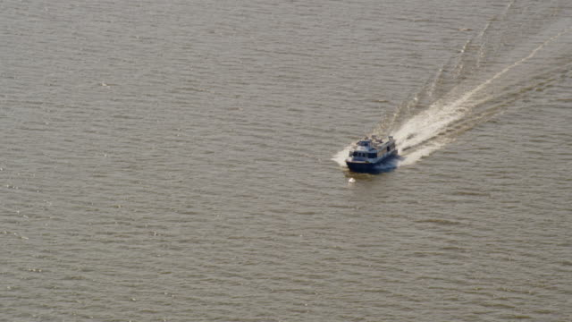 LONG AERIAL POV over small ferry boat on water