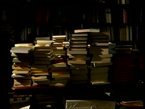 over smith's desk, covered in books and papers general view piles of paperbacks copies of smith's books in different languages smith looking at books - libro in brossura video stock e b–roll