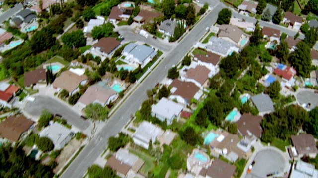 vídeos y material grabado en eventos de stock de aerial over suburban houses with blue swimming pools / san fernando valley, california - barrio con viviendas idénticas