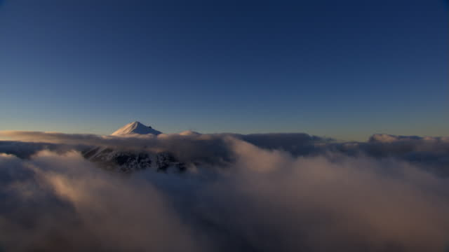 Over the clouds toward snowy peak