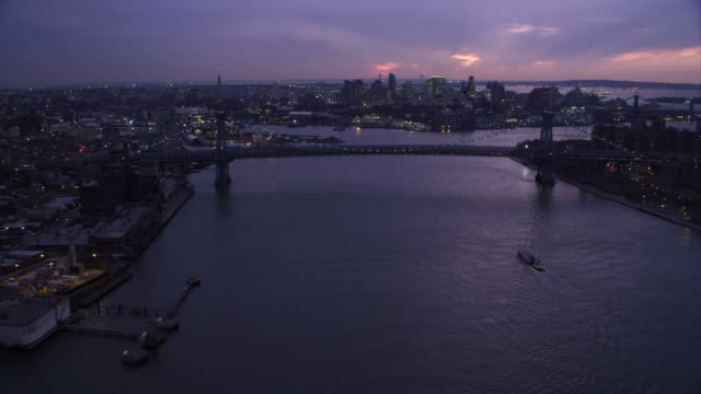 Over the East River, approaching Williamsburg Bridge at dusk. Shot in November 2011.