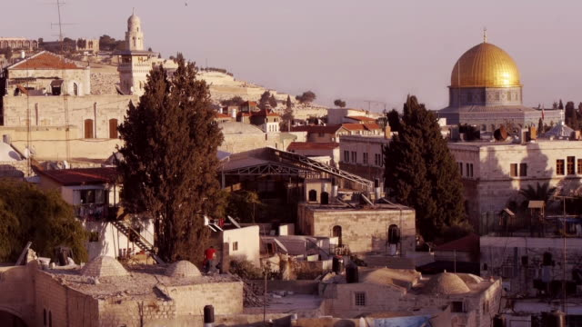 Over the roofs of Jerusalem Old City - Dome of the Rock and church in background.
