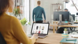 Over the Shoulder: Female Employee Browsed Through Online Retail Shopping Site. Office where Diverse Team of Young Professionals Work on Computers