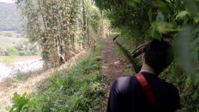stockvideo's en b-roll-footage met over de schouder van thaise jongeman op de rand van berg dia. - omkijken