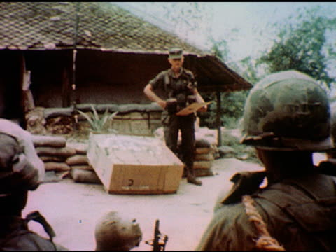/ over the shoulder of two seated soldiers commanding officer gives orders to group / cu of soldier in helmet holding gun on january 01 1967 in... - maschinengewehr stock-videos und b-roll-filmmaterial