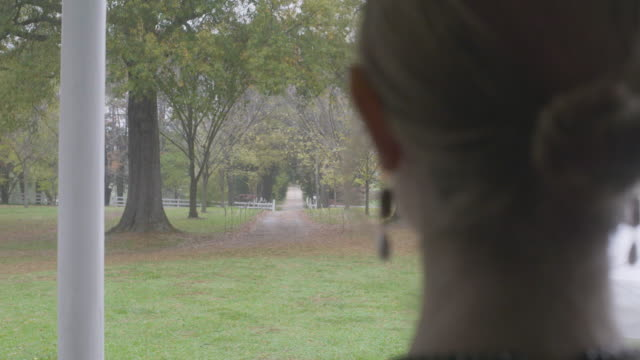 stockvideo's en b-roll-footage met over the shoulder reenactment shot of a tree-lined dirt road during the civil war era - 18e eeuwse stijl