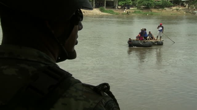 over the shoulder shot of a mexican national guard soldier watching a raft carrying people crossing the suchiate river near tapachula, mexico. - 肩越し点の映像素材/bロール