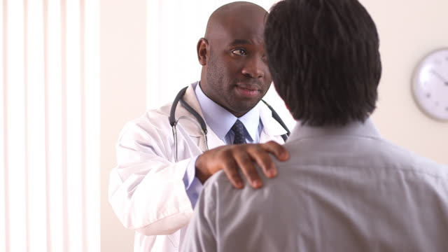 over the shoulder shot of doctor talking to patient - menschliches gelenk stock-videos und b-roll-filmmaterial